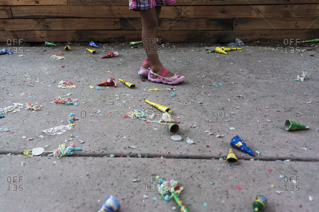 Party favors scattered around girl's feet