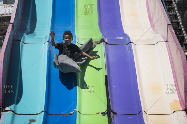 Boy swooping down giant theme park slide