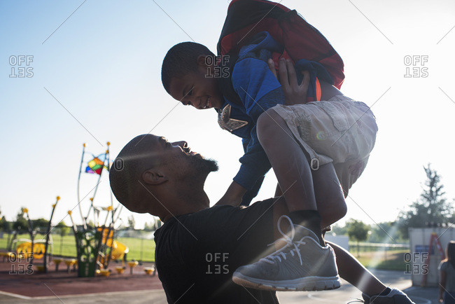 Father holding up son in sunny park