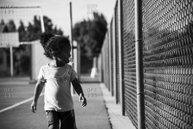 Toddler with pacifier looking through park chain link fence