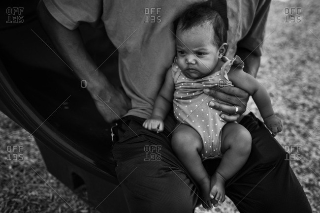 Black and white family portrait of concerned baby in father's lap