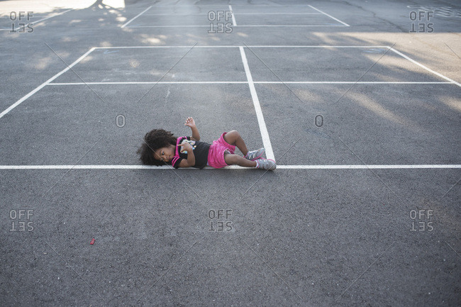 Little girl rolling round on outdoor basketball court