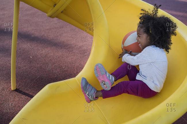 Preschooler sliding down spiral slide with basketball