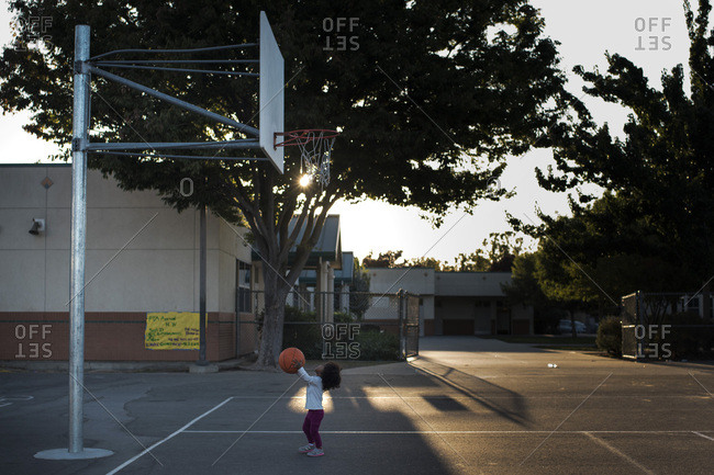Little girl aiming at basketball hoop