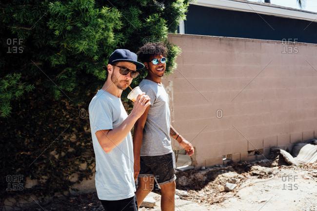 Friends walking down dirt track by wall