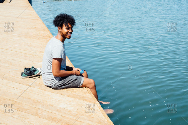 Man sitting by edge of water
