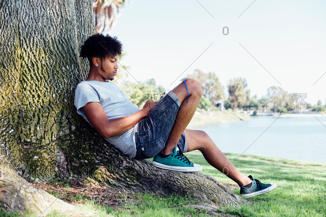 Man sitting on root of tree