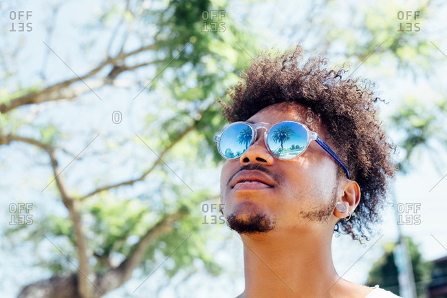 Man wearing sunglasses, looking up