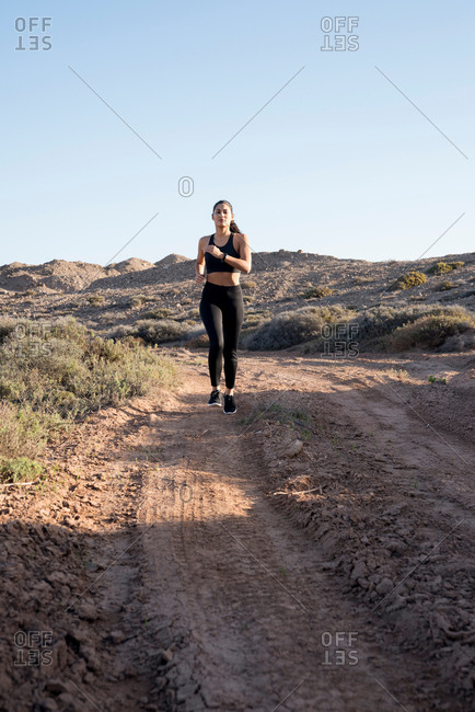 Young female runner running along dirt track in arid landscape, Las Palmas, Canary Islands, Spain