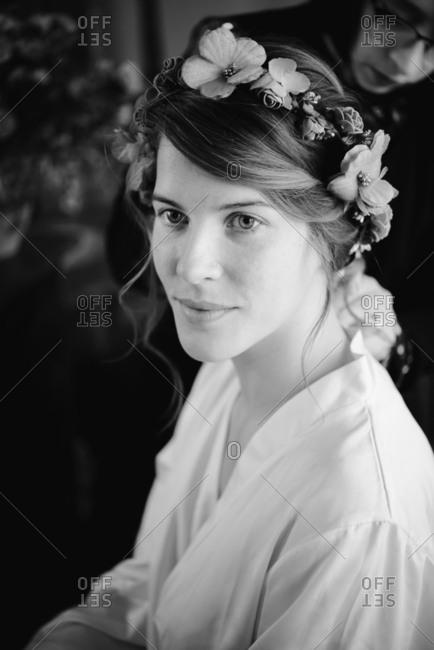 Bride preparing for wedding, hairstylist in background