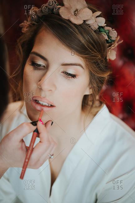 Bride having lip liner applied by make-up artist