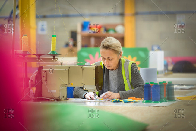 Female worker making cushions with sewing machine in factory