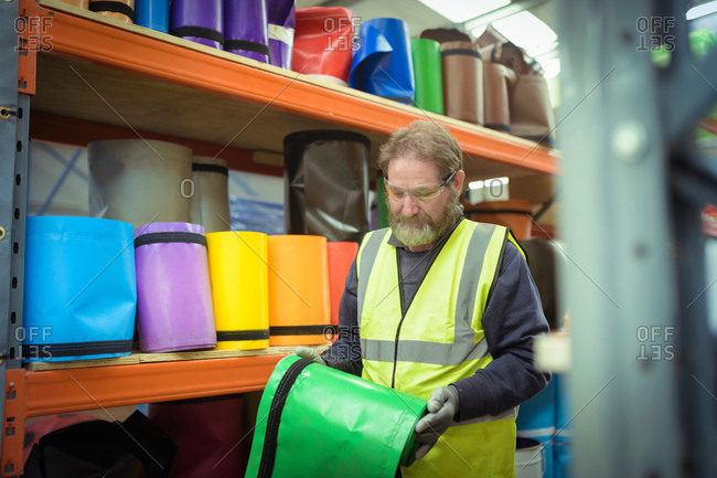 Worker selecting colored vinyl rolls in factory