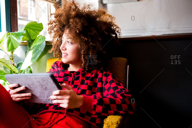 Young woman sitting indoors, using digital tablet