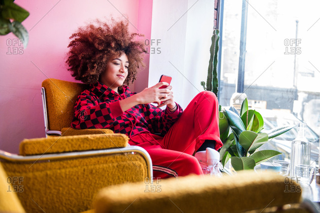 Young woman sitting indoors, using smartphone