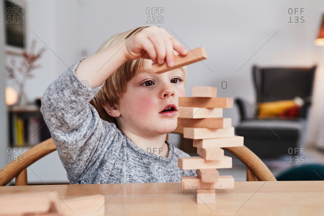 Portrait of young boy, building structure with wooden building blocks