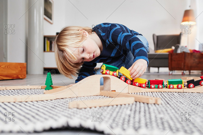 Young boy playing with toy train and track