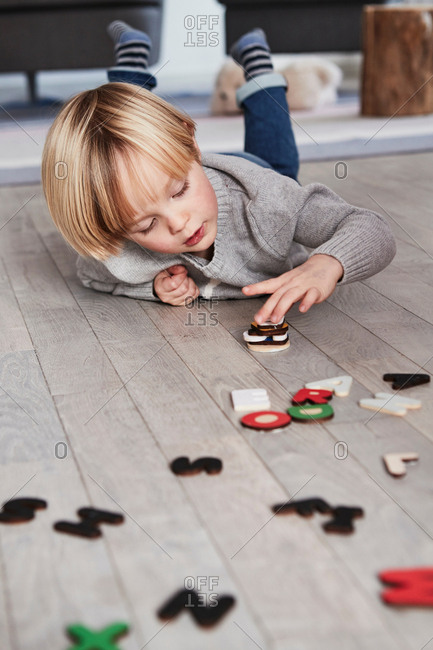 Young boy lying on floor, stacking magnetic letters