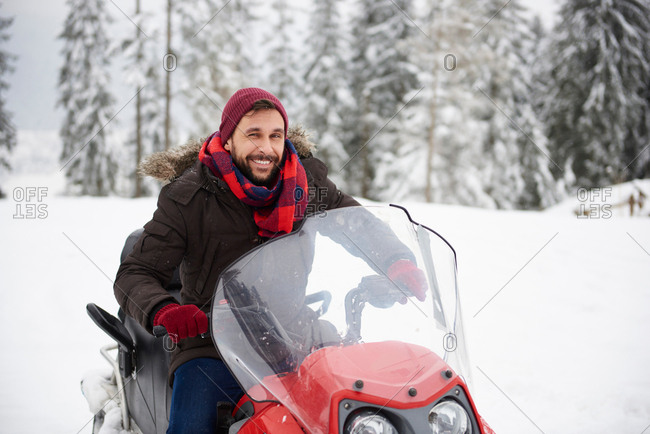 Young man riding snowmobile in winter