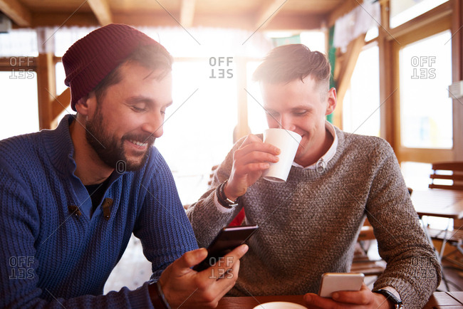 Young men smiling over text message on mobile phones