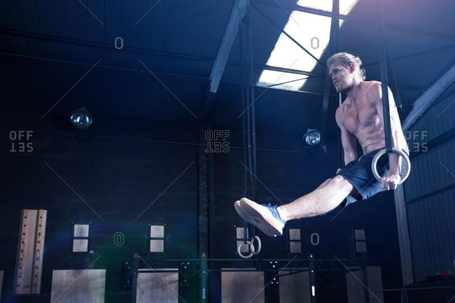 Man in gymnasium, balancing on gymnastic rings