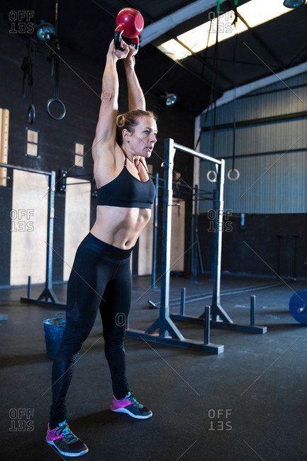 Woman exercising in gymnasium, using kettlebell