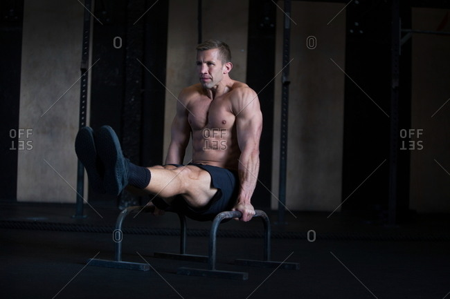 Man exercising in gymnasium, using parallel bars, in L-sit hold