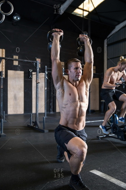 Two men exercising in gymnasium, using kettlebells and air resistance exercise bike