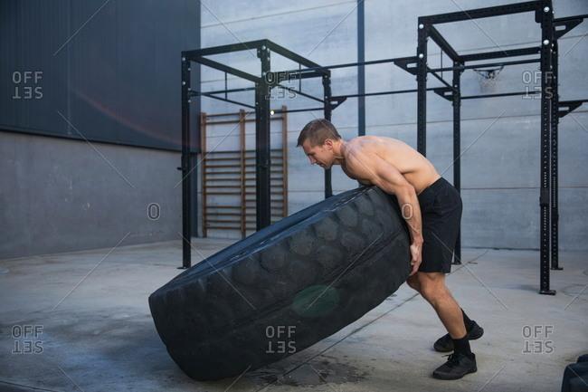 Man exercising in gymnasium, lifting tire