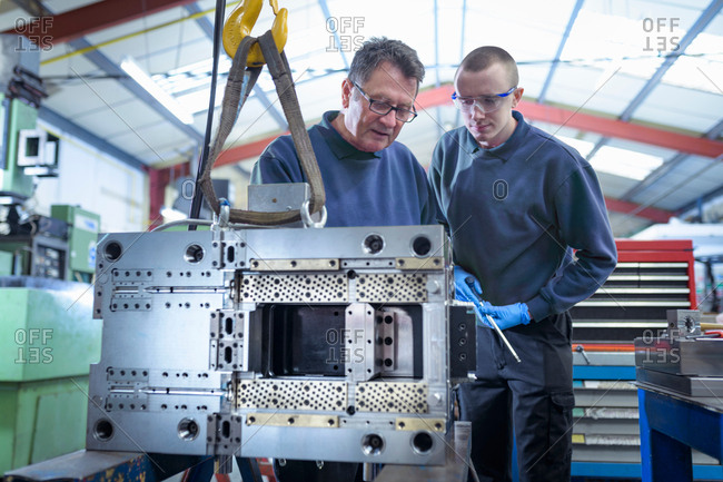 Engineer and apprentice working on mould for plastic injection in precision engineering factory