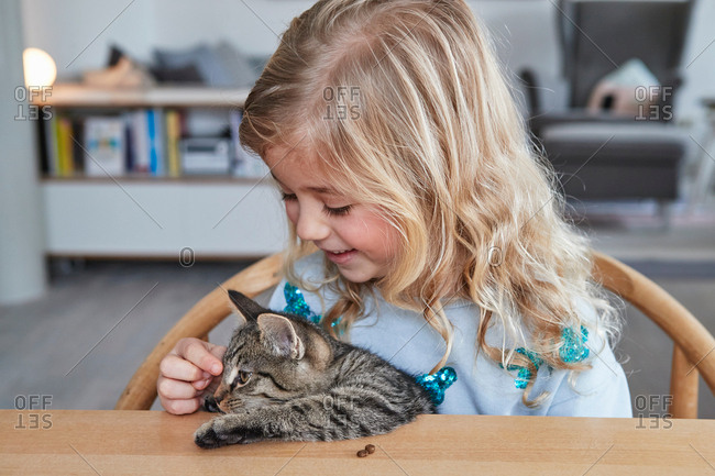Portrait of young girl, sitting at table, stroking pet cat