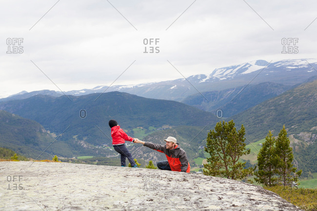 Boy helping hiker father over rock in mountain landscape, Jotunheimen National Park, Lom, Oppland, Norway