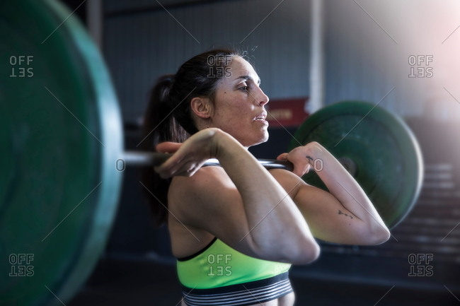 Woman exercising in gym, using barbell