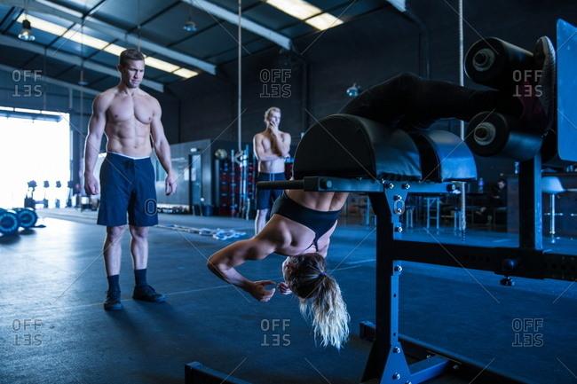 Three people exercising in gymnasium, using equipment