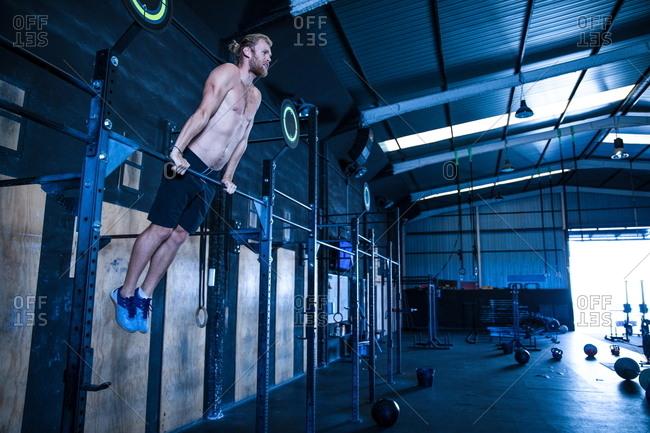 Man exercising in gymnasium, using pull up bars
