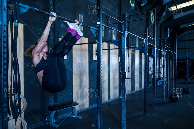 Woman exercising in gymnasium, using pull up bars
