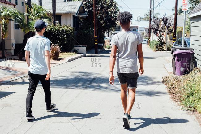 Friends walking down sunny street, Long Beach, California, US