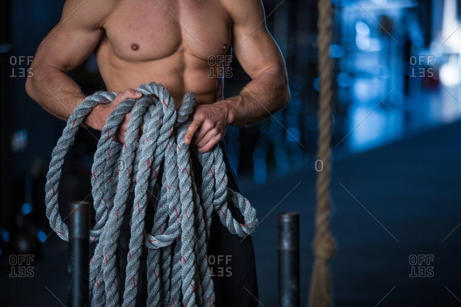 Man exercising in gymnasium, holding rope, preparing for sled training, mid section