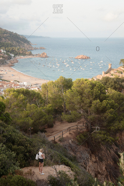 Woman standing on rock, looking at view, elevated view, Tossa de mar, Catalonia, Spain