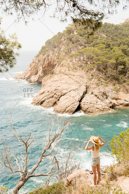 Woman along coastline, looking at view, elevated view, Tossa de mar, Catalonia, Spain