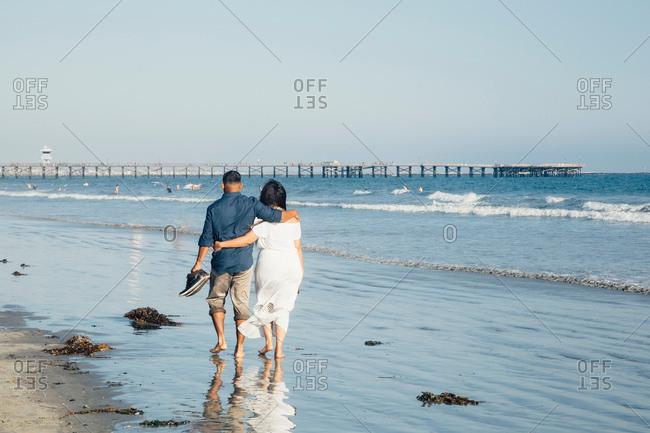 Couple walking along beach, barefoot, rear view, Seal Beach, California, USA