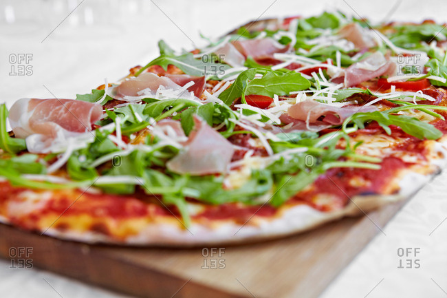 Fresh pizza with rocket and parma ham on chopping board