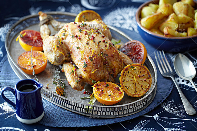 Roast chicken with glazed citrus fruits on serving tray