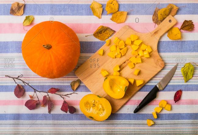 Still life of pumpkin, chopping board and chopped pumpkin, overhead view