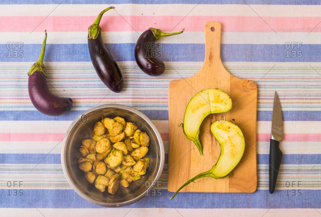 Aubergines, with sliced aubergine on chopping board and pan with prepared food