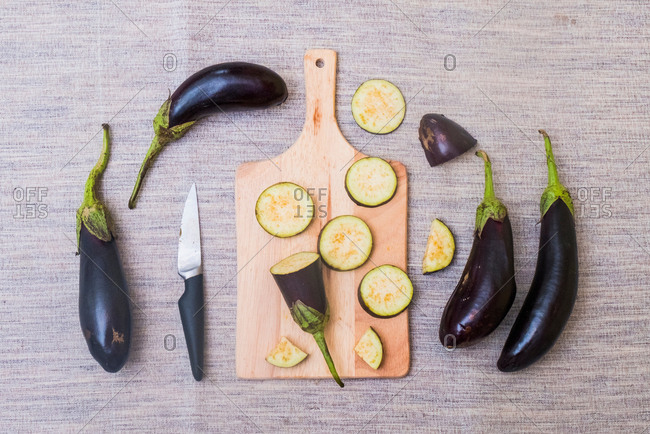 Slices of aubergine on chopping board, with knife and whole aubergines, overhead view