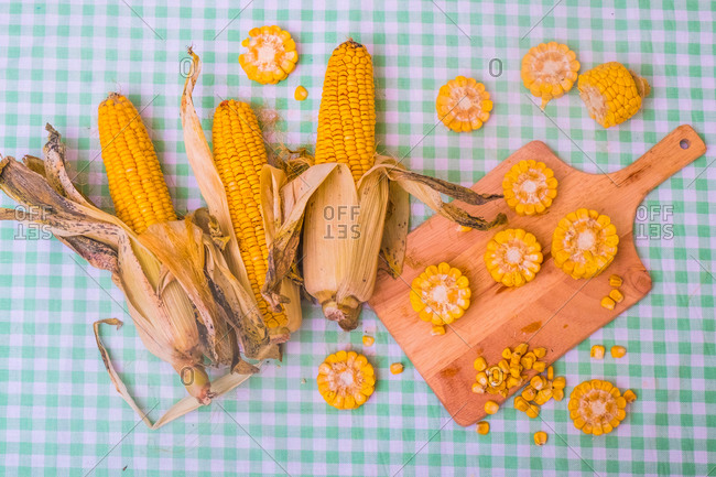 Sliced corn on the cob on chopping board, with whole corn on cob, overhead view