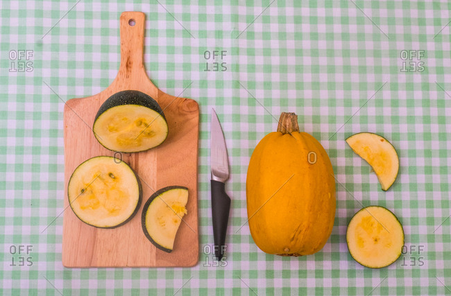 Two varieties of squash, one whole, the other sliced on chopping board, elevated view