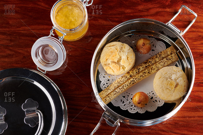 Bread basket of biscuits, cheese puffs and bread sticks served in a small tin with a side of sweet honey marmalade