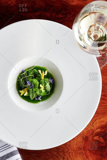 Overhead view of gastronomic juice dish served with flavored vegetable puree and presented with edible flowers and herbaceous leaves